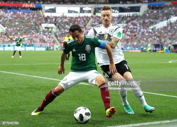 Andres Guardado of Mexico is challenged by Marco Reus of Germany during the 2018 FIFA World Cup Russia group F match between Germany and Mexico at...