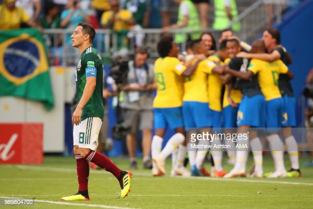 Andres Guardado of Mexico looks dejected as Roberto Firmino of Brazil celebrates after scoring a goal to make it 20 during the 2018 FIFA World Cup...