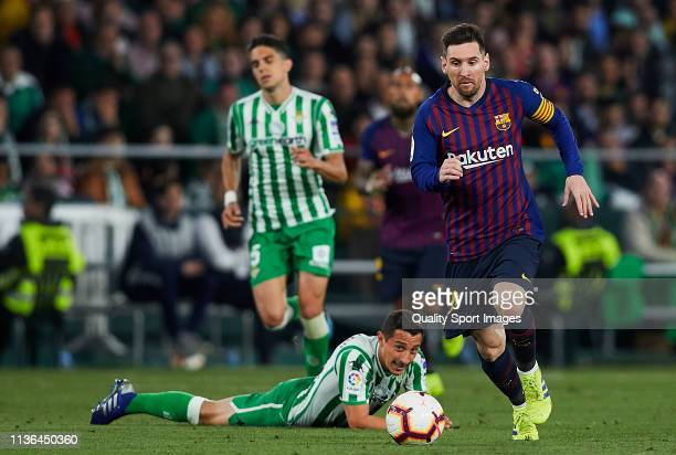 Andres Guardado of Real Betis competes for the ball with Lionel Messi of FC Barcelona during the La Liga match between Real Betis Balompie and FC...