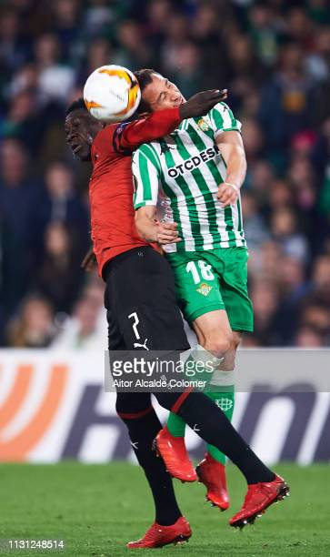 Andres Guardado of Real Betis duels for the ball with Ismaila Sarr of Stade Rennais during the UEFA Europa League Round of 32 Second Leg match...
