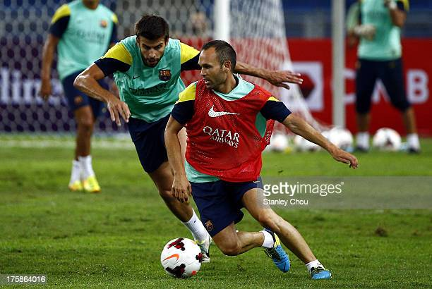 Andres Inesta and Gerard Pique of Barcelona FC battle for the ball during Barcelona FC training session at Bukit Jalil National Stadium on August 9...