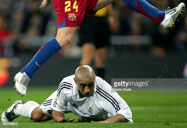 Andres Inesta of Barcelona jumps over Roberto Carlos of Real Madrid during a Primera Liga match between Real Madrid and FC Barcelona at the Bernabeu...