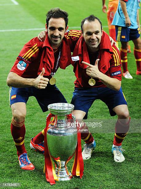 Andres Iniesta and Juanfran of Spain pose with the trophy following victory in the UEFA EURO 2012 final match between Spain and Italy at the Olympic...