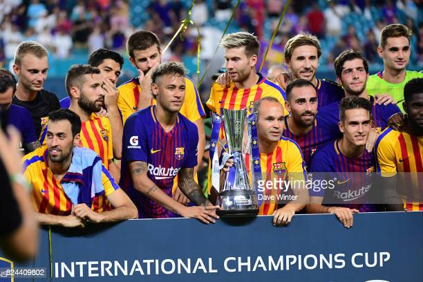 Andres Iniesta and Neymar Jr of Barcelona lift the tournament winner's trophy after the International Champions Cup match between Barcelona and Real...