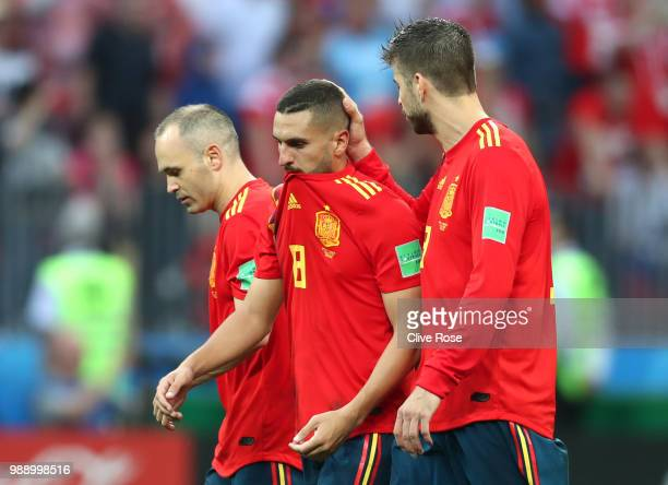 Andres Iniesta Koke and Gerard Pique of Spain look dejected following their sides defeat in the 2018 FIFA World Cup Russia Round of 16 match between...