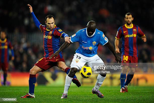 Andres Iniesta of Barcelona duels for the ball against Modeste M'Bami of Almeria during the Copa del Rey Semi Final First Leg match between Barcelona...