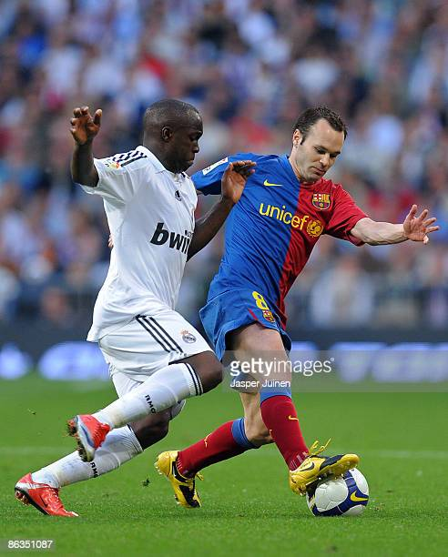 Andres Iniesta of Barcelona duels for the ball with Lass Diarra of Real Madrid during the La Liga match between Real Madrid and Barcelona at the...