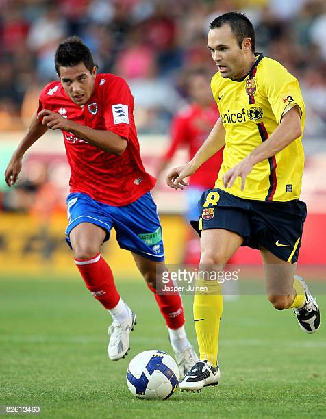Andres Iniesta of Barcelona duels for the ball with Mario Martinez of Numancia during the La Liga match between Numancia and Barcelona at the Los...