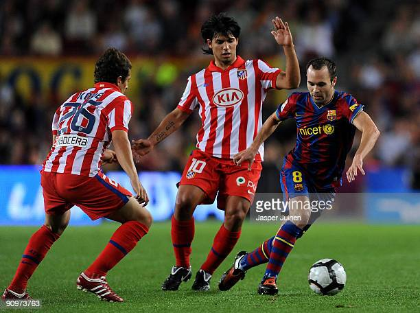 Andres Iniesta of Barcelona duels for the ball with Sergio Aguero and Koke of Atletico Madrid during the La Liga match between Barcelona and Atletico...