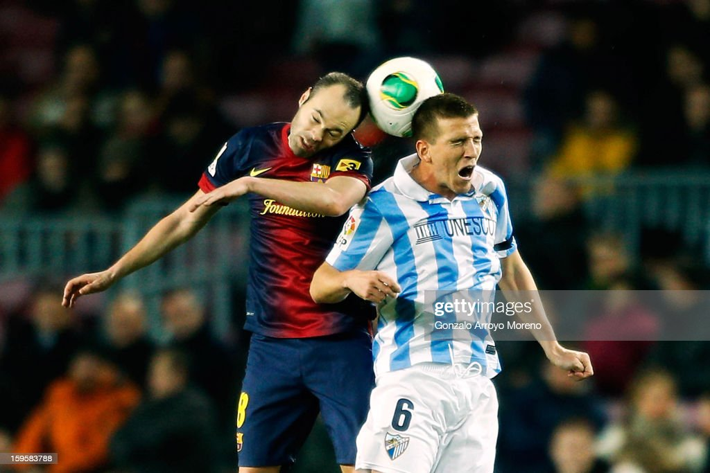 Andres Iniesta (L) of Barcelona FC saves on a header with Ignacio Camacho (R) of Malaga CF during the Copa del Rey Quarter Final match between Barcelona FC and Malaga CF at Camp Nou on January 16, 2013 in Barcelona, Spain.