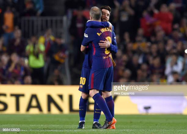 Andres Iniesta of Barcelona is embraced by Lionel Messi as he is substituted in his final El Clasico during the La Liga match between Barcelona and...