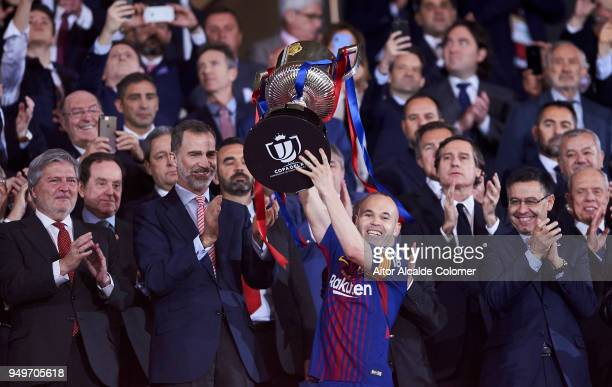 Andres Iniesta of Barcelona lifts the trophy in his last final for the club after his teams win during the Spanish Copa del Rey match between...