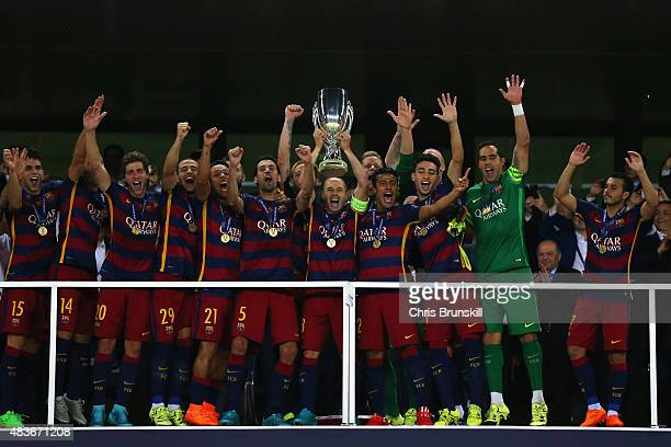 Andres Iniesta of Barcelona lifts the UEFA Cup trophy as Barcelona celebrate victoy during the UEFA Super Cup between Barcelona and Sevilla FC at...