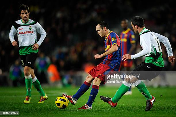 Andres Iniesta of Barcelona passes the ball under pressure from Marc Torrejon of Racing Santander during the La Liga match between Barcelona and...