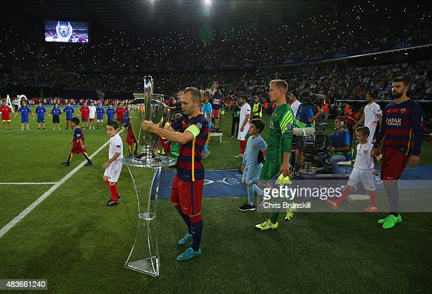 Andres Iniesta of Barcelona places the Champions league trophy pitchside prior to the UEFA Super Cup between Barcelona and Sevilla FC at Dinamo Arena...