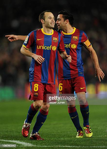 Andres Iniesta of Barcelona runs past his teammate Xavi Hernandez after scoring his sides third goal during the la liga match between Barcelona and...