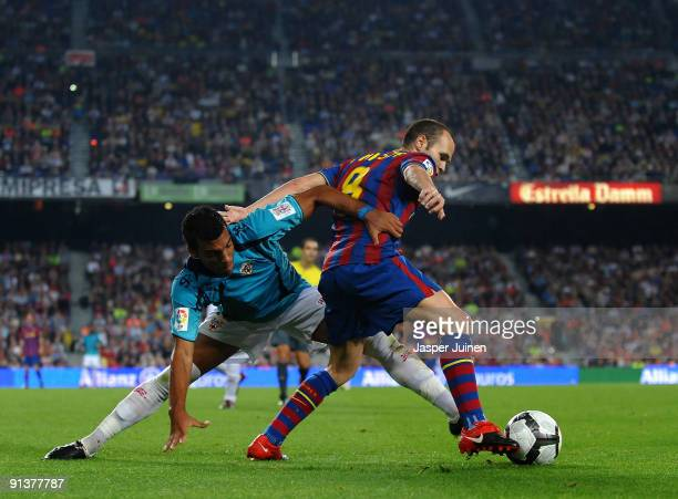 Andres Iniesta of Barcelona shields the ball from Michel Macedo Rocha of Almeria during the La Liga match between Barcelona and Almeria at the Camp...