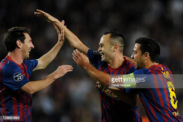 Andres Iniesta of FC Barcelona celebrates with his teammates Lionel Messi and Xavi Hernandez after scoring the opening goal during the UEFA Champions...