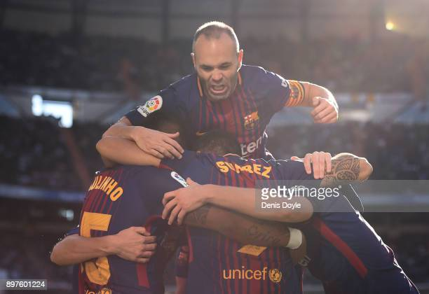 Andres Iniesta of FC Barcelona celebrates with Luis Suarez after Suarez scored their 1st goal during the La Liga match between Real Madrid and...