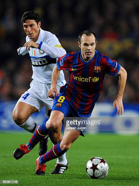 Andres Iniesta of FC Barcelona competes for the ball with Javier Zanetti captain of Inter Milan during the UEFA Champions League group F match...