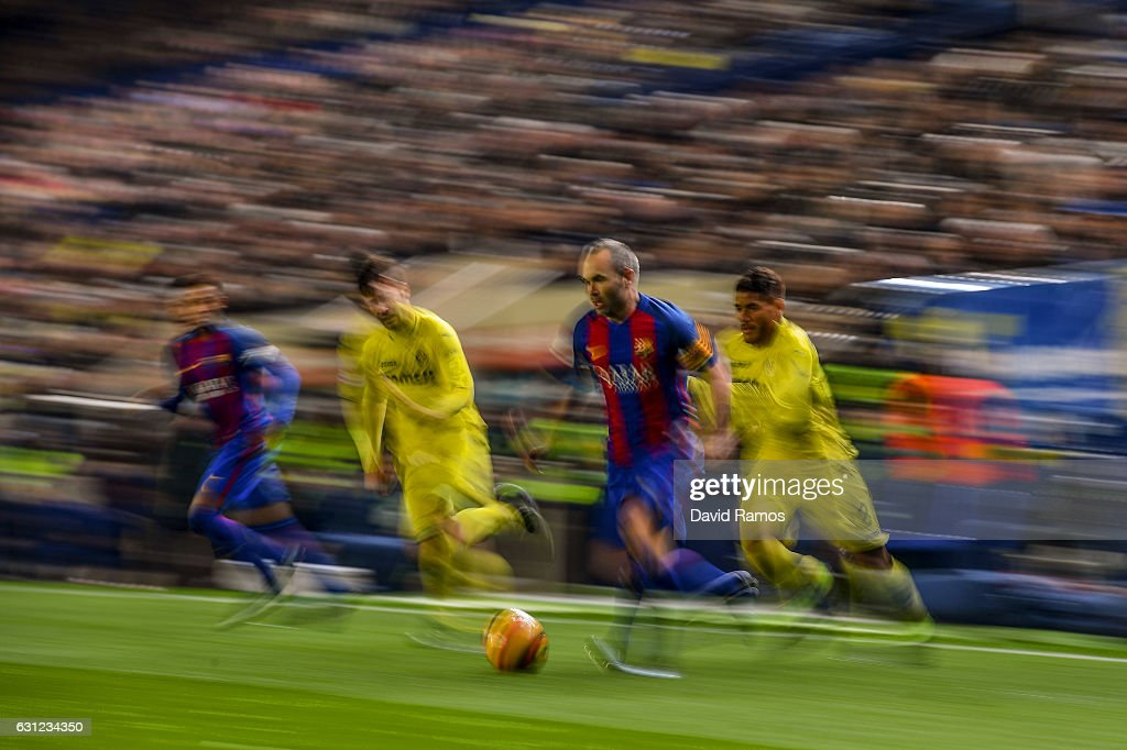 Andres Iniesta of FC Barcelona competes for the ball with Manu Trigueros (C) and Jonathan dos Santos of Villarreal CF during the La Liga match between Villarreal CF and FC Barcelona at Estadio de la Ceramica stadium on January 8, 2017 in Villarreal, Spain.