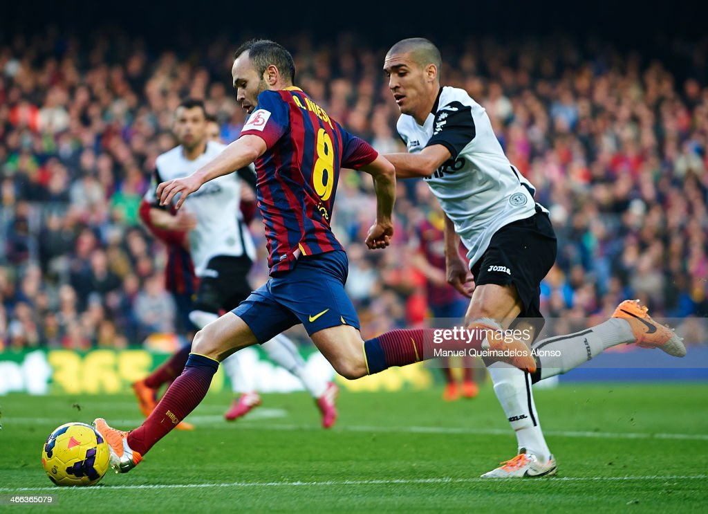 Andres Iniesta of FC Barcelona competes for the ball with Oriol Romeu (L) of Valencia CF during the La Liga match between FC Barcelona and Valencia CF at Camp Nou on February 1, 2014 in Barcelona, Spain.