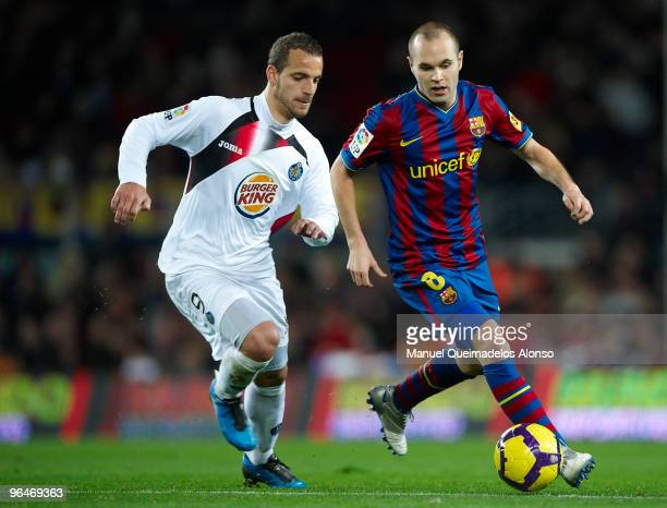 Andres Iniesta of FC Barcelona competes for the ball with Roberto Soldado of Getafe during the La Liga match between Barcelona and Getafe at Camp Nou...