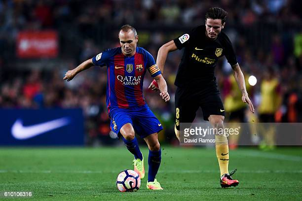 Andres Iniesta of FC Barcelona competes for the ball with Saul Niguez of Club Atletico de Madrid during the La Liga match between FC Barcelona and...