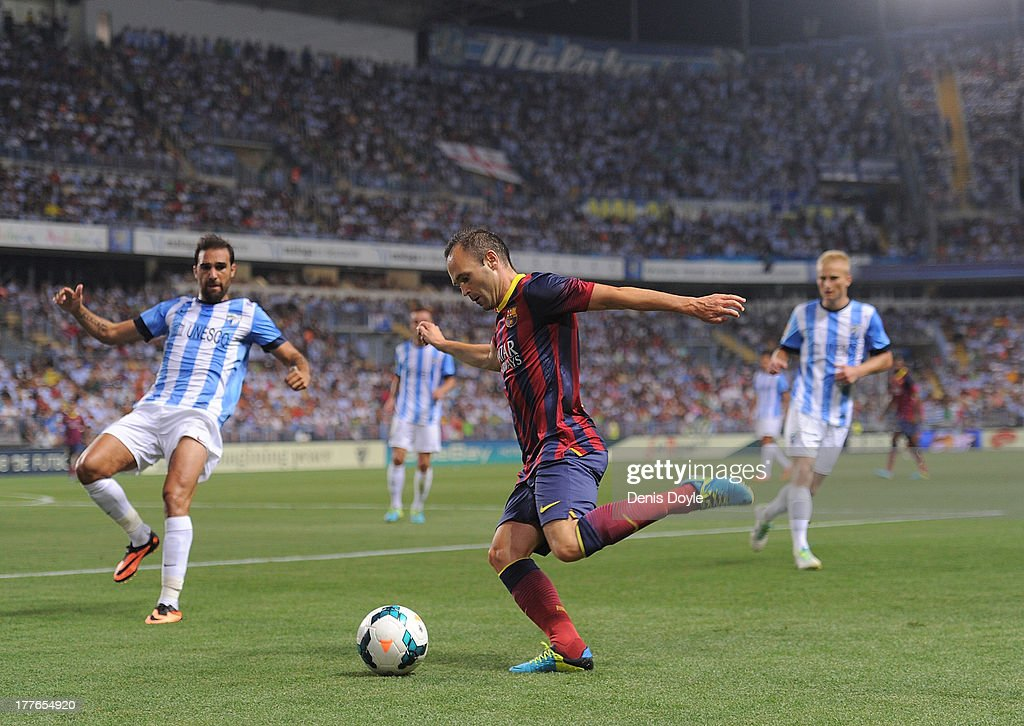Andres Iniesta (C) of FC Barcelona crosses the ball during the La Liga match between Malaga CF and FC Barcelona at La Rosaleda Stadium on August 25, 2013 in Malaga, Spain.