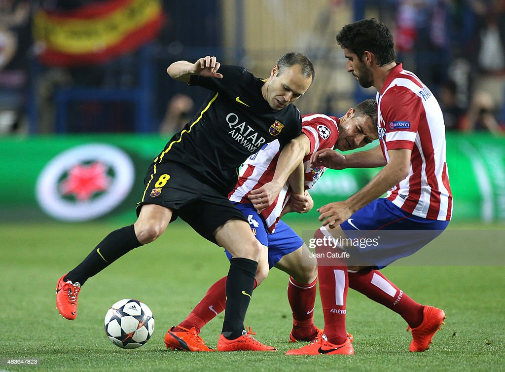 Andres Iniesta of FC Barcelona, Gabi Fernandez of Atletico Madrid and Raul Garcia of Atletico Madrid in action during the UEFA Champions League quarter final match between Club Atletico de Madrid and FC Barcelona at Vicente Calderon stadium on April 9, 2014 in Madrid, Spain.