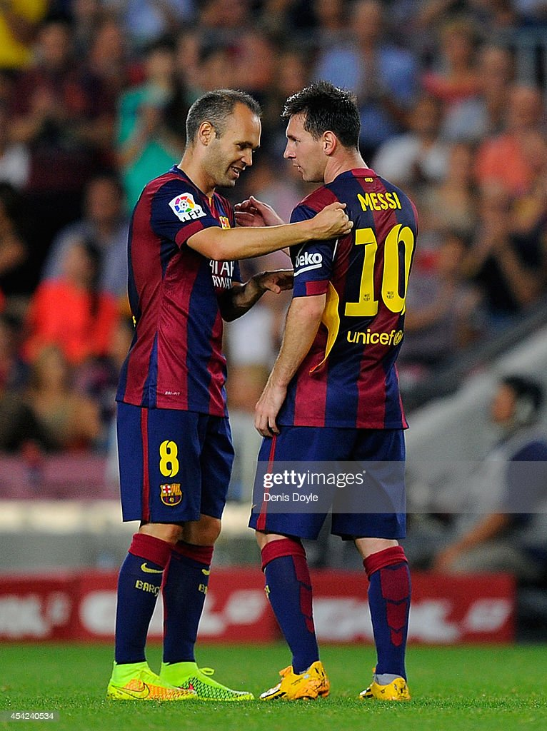 Andres Iniesta of FC Barcelona hands over the captian's armband to Lionel Messi during the La Liga match between FC Barcelona and Elche FC at Camp Nou stadium on August 24, 2014 in Barcelona, Spain.