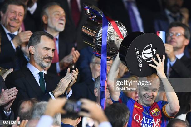 Andres Iniesta of FC Barcelona holds up the trophy as King Felife VI of Spain acknowledges him after winning the Copa Del Rey Final between FC...