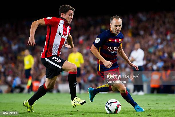 Andres Iniesta of FC Barcelona runs past Gorka Elustondo of Athletic Club during the Spanish Super Cup second leg match between FC Barcelona and...