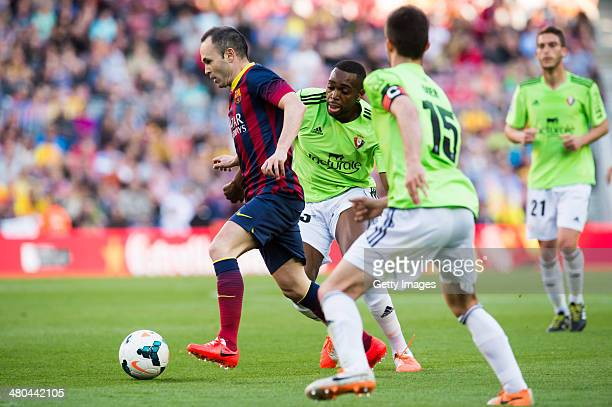 Andres Iniesta of FC Barcelona runs with the ball between Raoul Cedric Loe and Oier Sanjurjo of CA Osasuna during the La Liga match between FC...