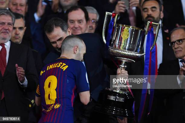 Andres Iniesta of FC Barcelona shakes hands with King Felipe VI of Spain before lifting the trophy after winning with his team the Spanish Copa del...