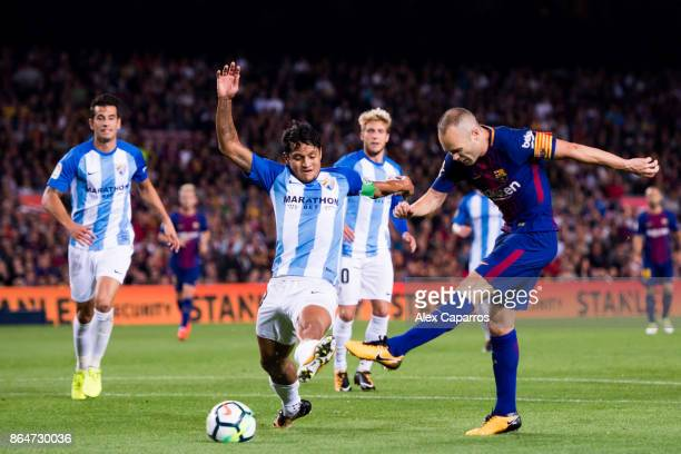 Andres Iniesta of FC Barcelona shoots the ball under pressure from Roberto Rosales of Malaga CF and scores his team's second goal during the La Liga...