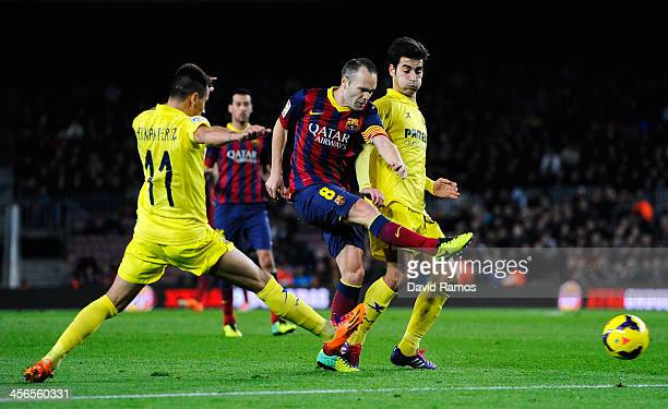 Andres Iniesta of FC Barcelona shoots towards goal under a challenge by Hernan Perez and Manu Trigueros of Villarreal CFduring the La Liga match...