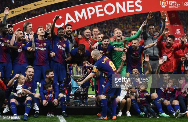 Andres Iniesta of FC Barcelona shows the trophy to teammate Lionel Messi after beating Sevilla 50 in the Spanish Copa del Rey Final match between...