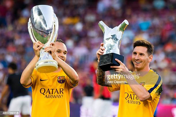 Andres Iniesta of FC Barcelona shows the UEFA Super Cup champions and his teammate Lionel Messi shows the UEFA Best Player in Europe of 2014/2015...