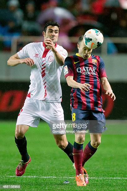 Andres Iniesta of FC Barcelona wins the header after Vicente Iborra of Sevilla FC during the La Liga match between Sevilla FC and FC Barcelona at...