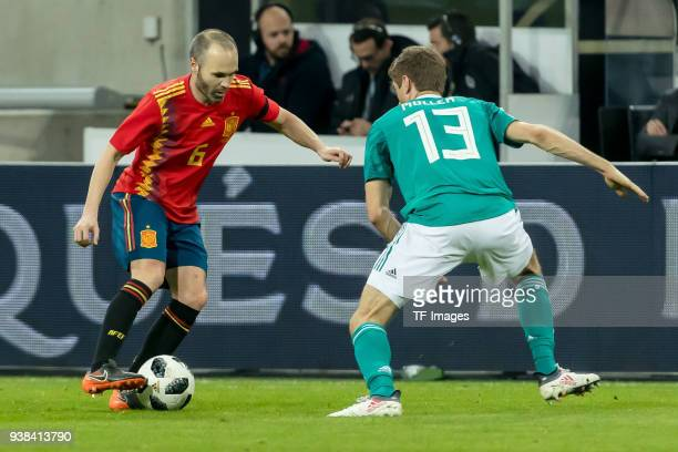 Andres Iniesta of Spain and Thomas Mueller of Germany battle for the ball during the international friendly match between Germany and Spain at...