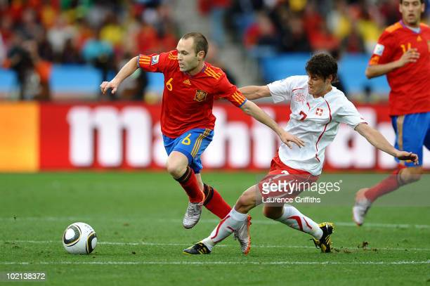 Andres Iniesta of Spain attempts to hold off Tranquillo Barnetta of Switzerland during the 2010 FIFA World Cup South Africa Group H match between...