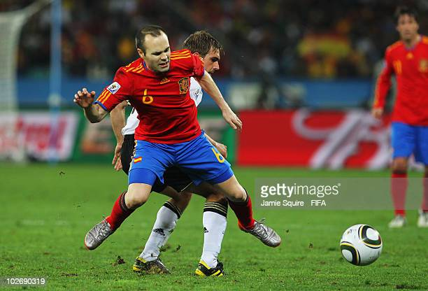 Andres Iniesta of Spain battles for the ball with Philipp Lahm of Germany during the 2010 FIFA World Cup South Africa Semi Final match between...
