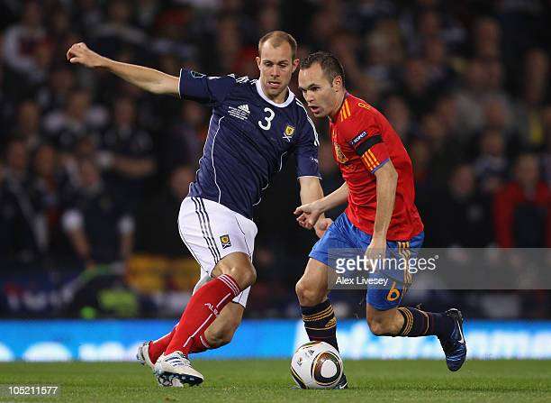 Andres Iniesta of Spain beats Steven Whittaker of Scotland during the UEFA EURO 2012 Group I Qualifier match between Scotland and Spain at Hampden...