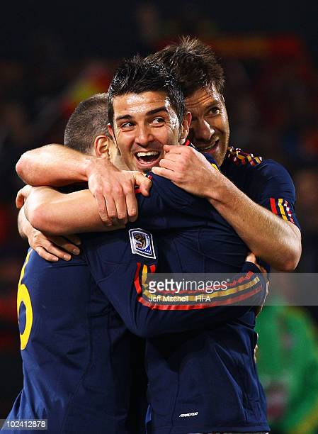 Andres Iniesta of Spain celebrates scoring with David Villa and Xabi Alonso during the 2010 FIFA World Cup South Africa Group H match between Chile...