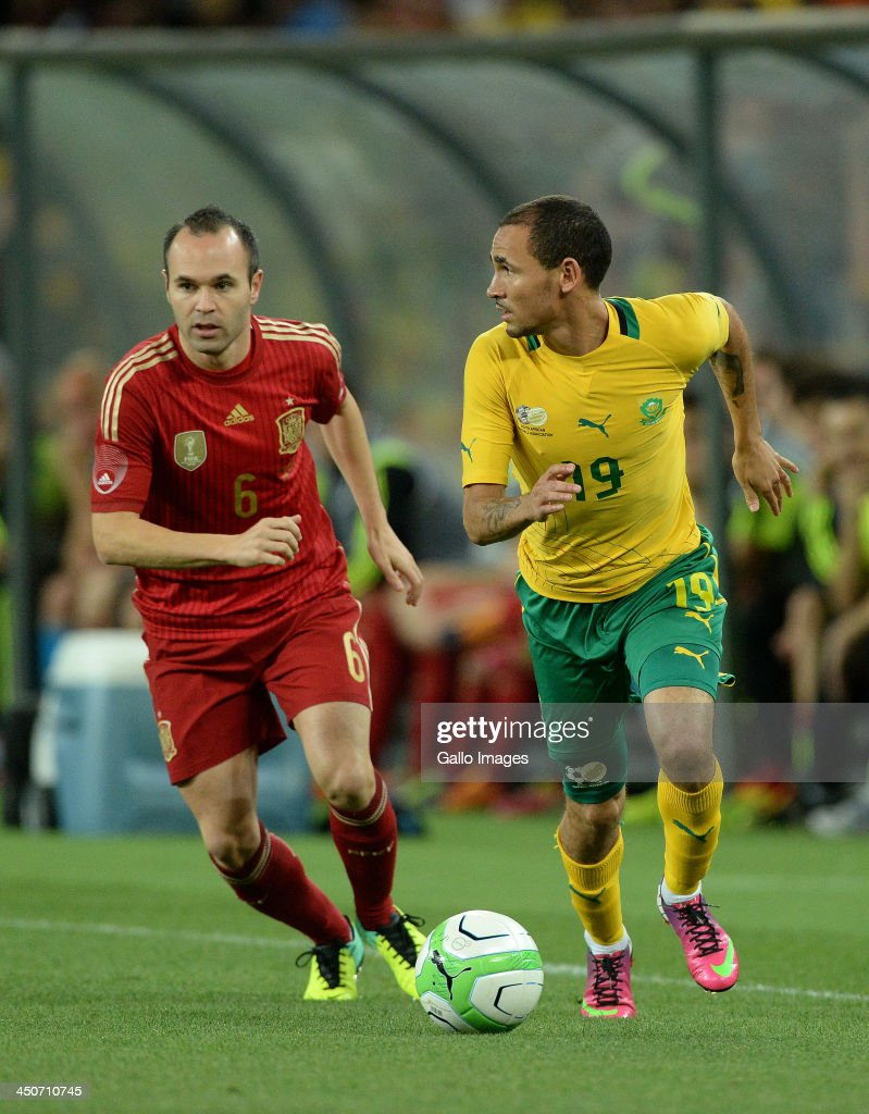 Andres Iniesta of Spain competes for the ball with Daylon Claasen of South Africa during the International friendly match between South Africa and Spain at Soccer City Stadium on November 19, 2013 in Johannesburg, South Africa.
