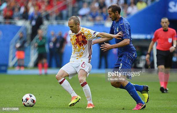 Andres Iniesta of Spain controls the ball under pressure of Giorgio Chiellini of Italy during the UEFA EURO 2016 round of 16 match between Italy and...