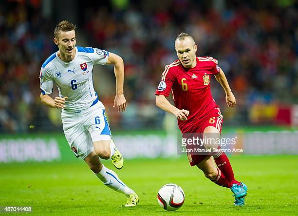 Andres Iniesta of Spain duels for the ball with Jan Gregus of Slovakia during the Spain v Slovakia EURO 2016 Qualifier at Carlos Tartiere on...