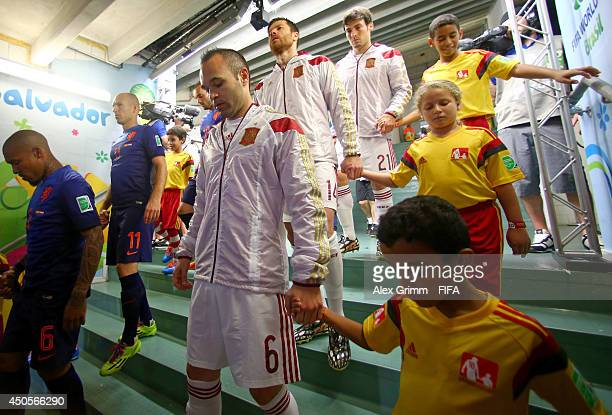 Andres Iniesta of Spain enters the pitch with player escorts prior to the 2014 FIFA World Cup Brazil Group B match between Spain and Netherlands at...