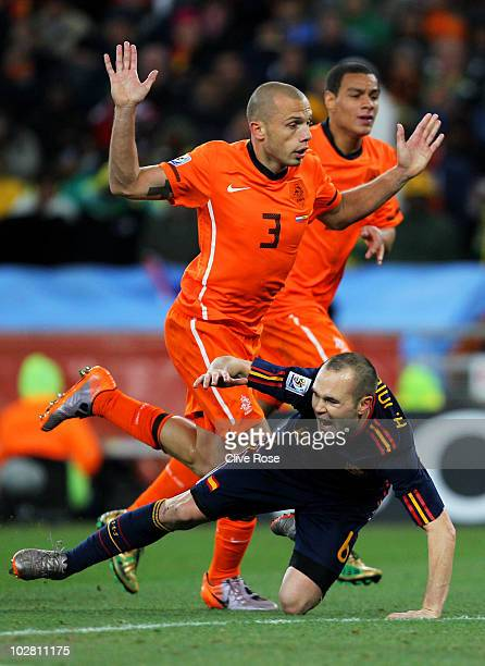 Andres Iniesta of Spain falls under the challenge of John Heitinga of the Netherlands which results in Heitinga being shown a second yellow card and...